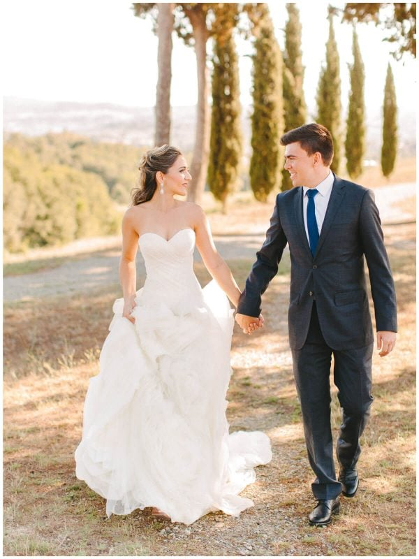 bride and groom walk in a dirt road in tuscany