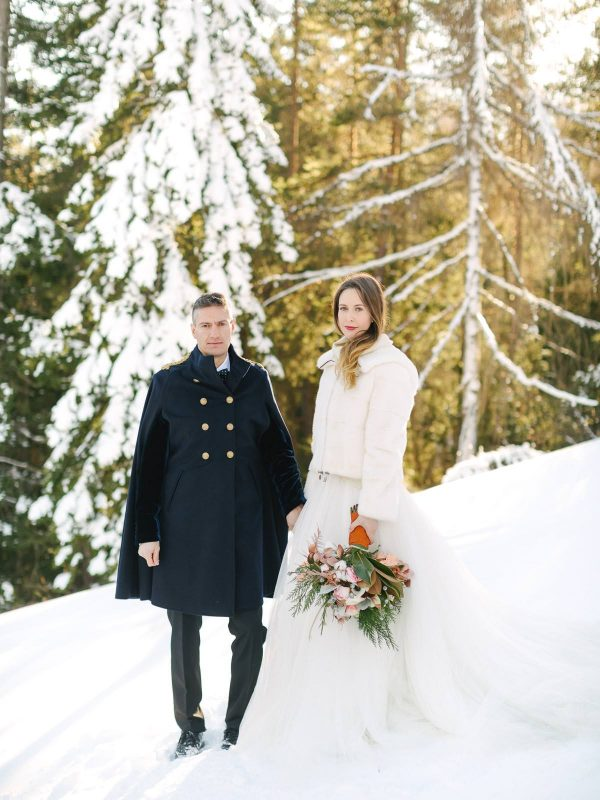 newlyweds' portrait among the snow in dolomites italian alps