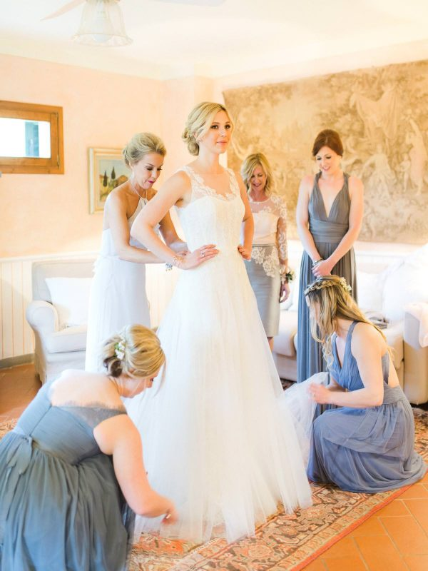 bridesmaids helping the bride to get dressed