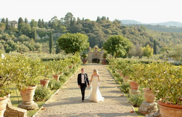 couple walk in the garden of villa di lilliano