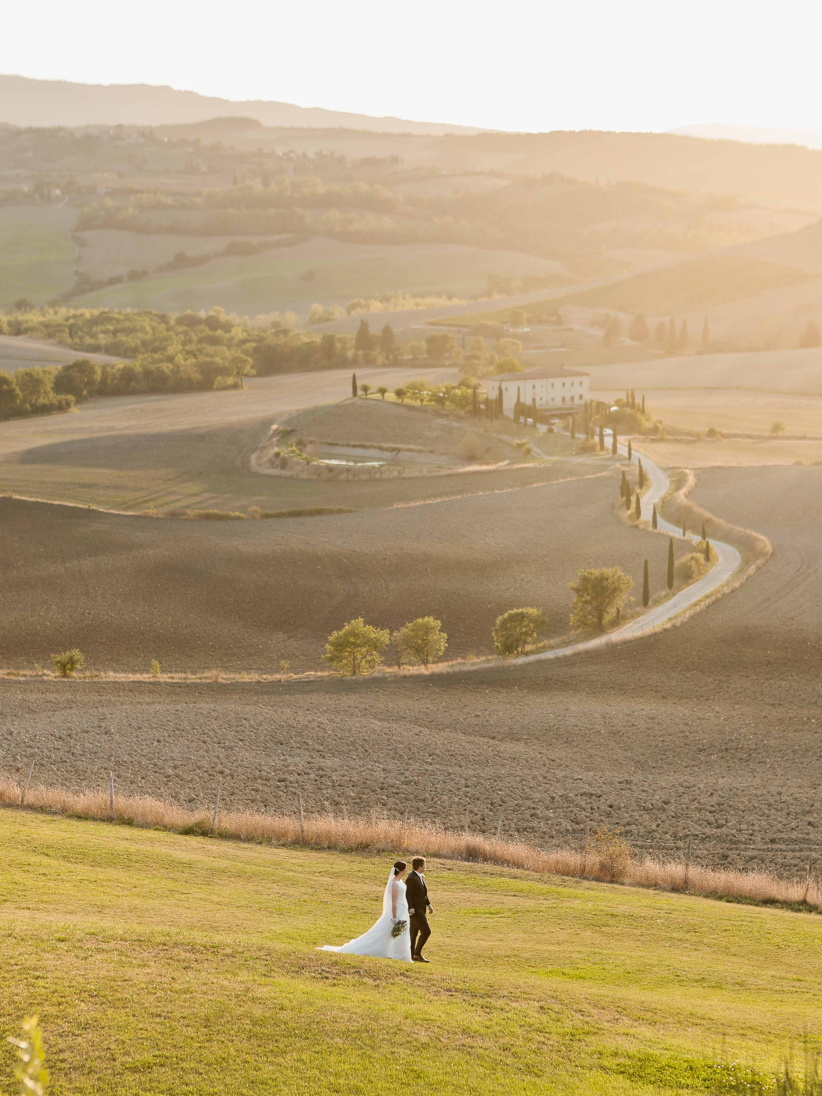 bride and groom walk in the fields of tuscany after their elopement