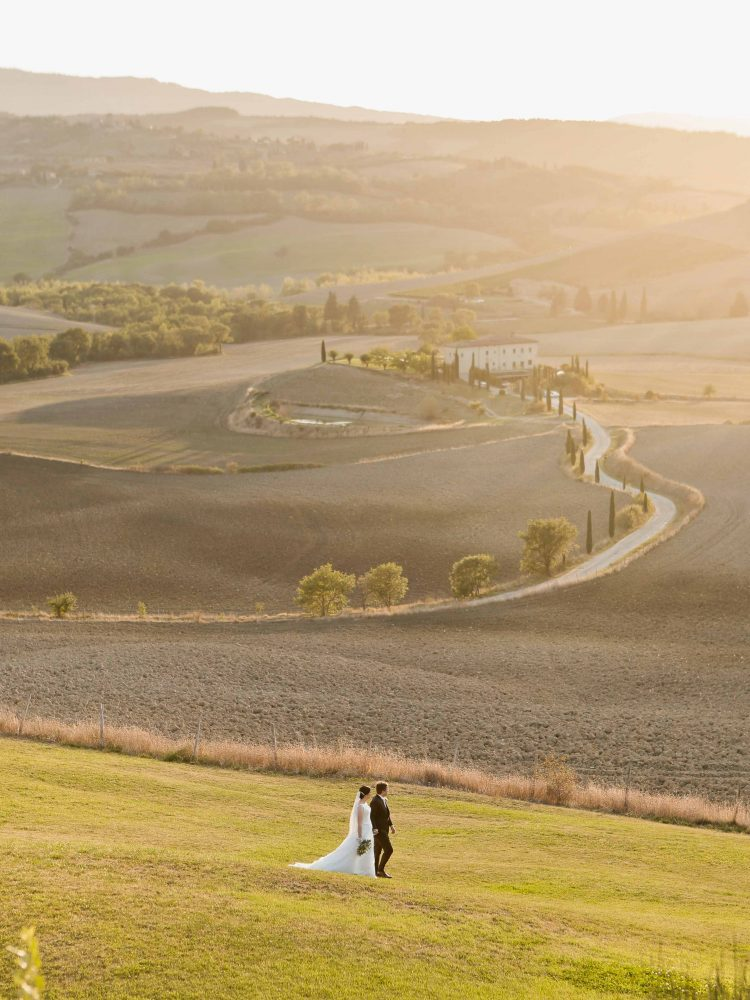 bride and groom stroll in the fields of tuscany after the elopement