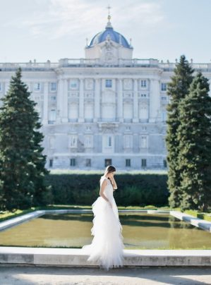 bride posing with the royal palace of madrid as the backdrop