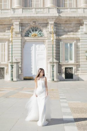 bride walking with the gate of the royal palace of madrid in the background