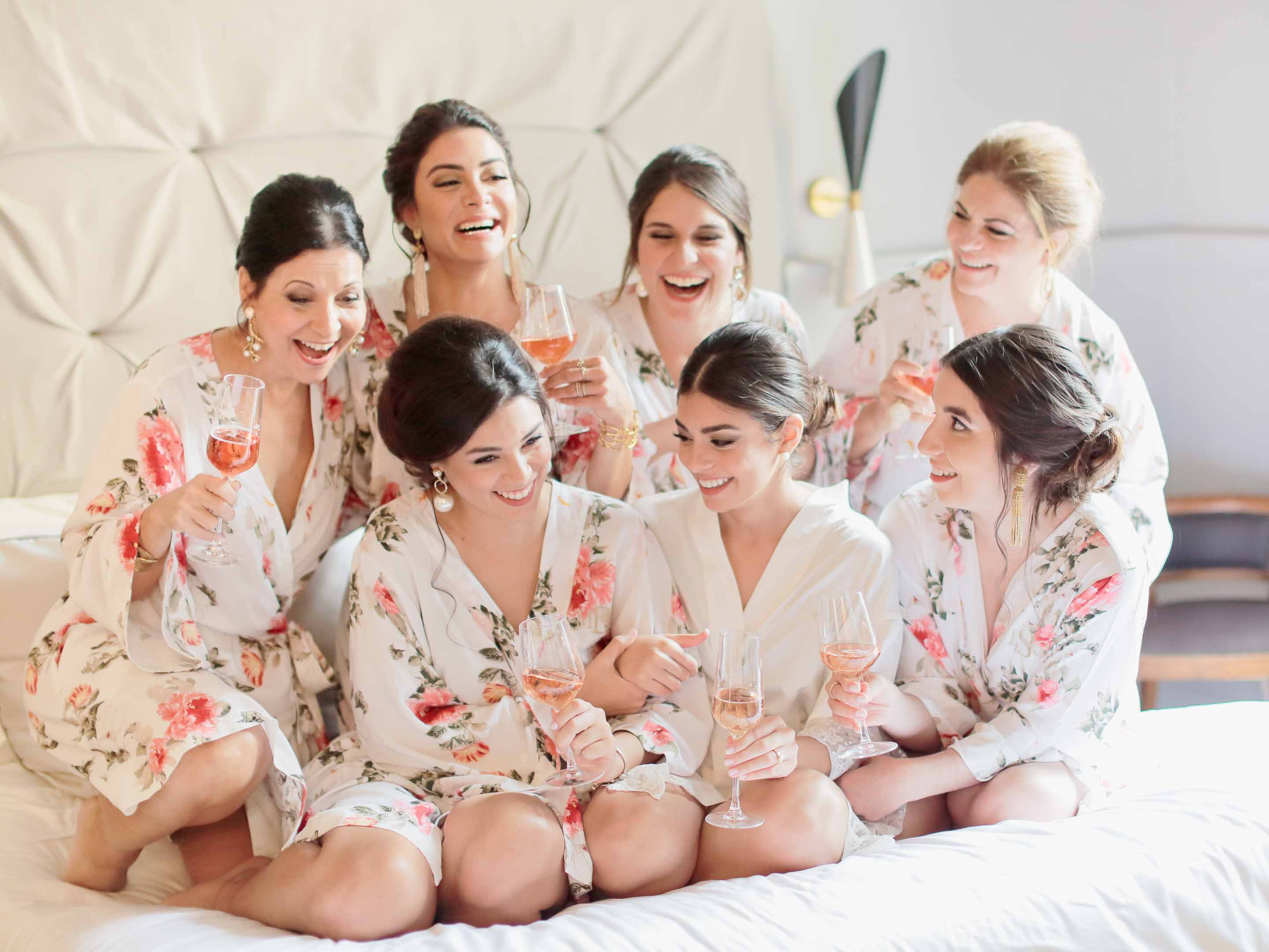 bride toasting the bridesmaids before stepping into her dress