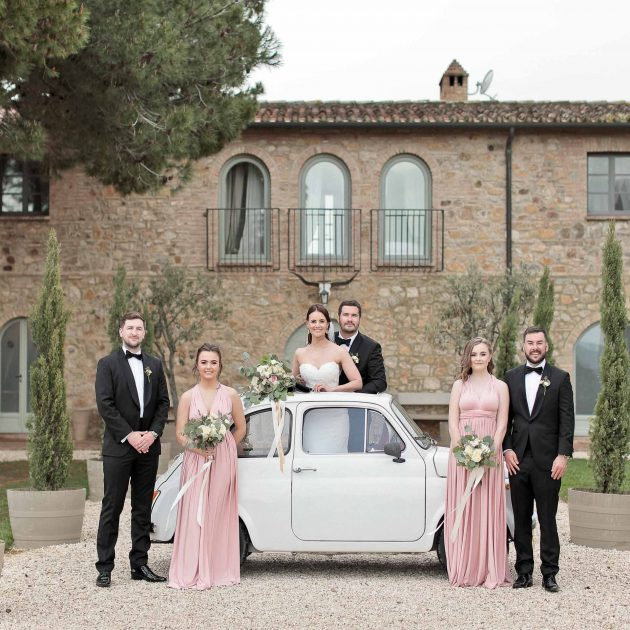 newlyweds toghether with bridesmaids and groomsmen posing for a photo with an old fiat cinquecento
