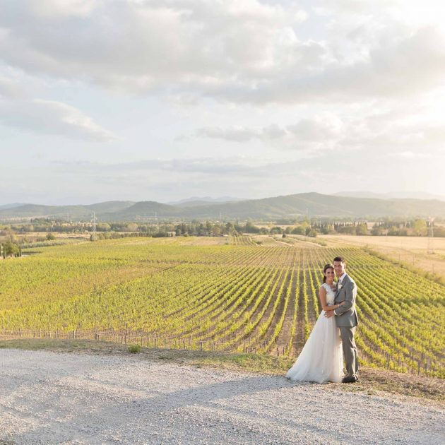 bride and groom posing for the photographer with maremma behind their shoulders
