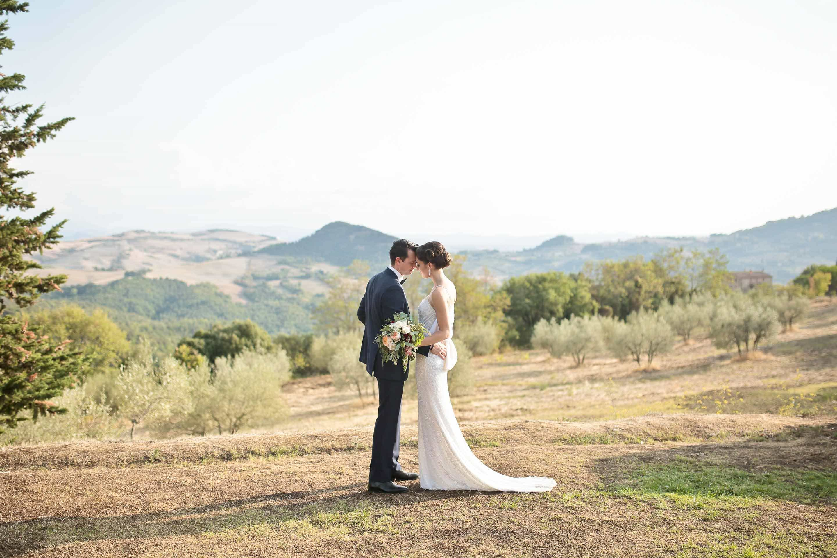 bride and groom joining their heads together with the landscape of tuscany in the background