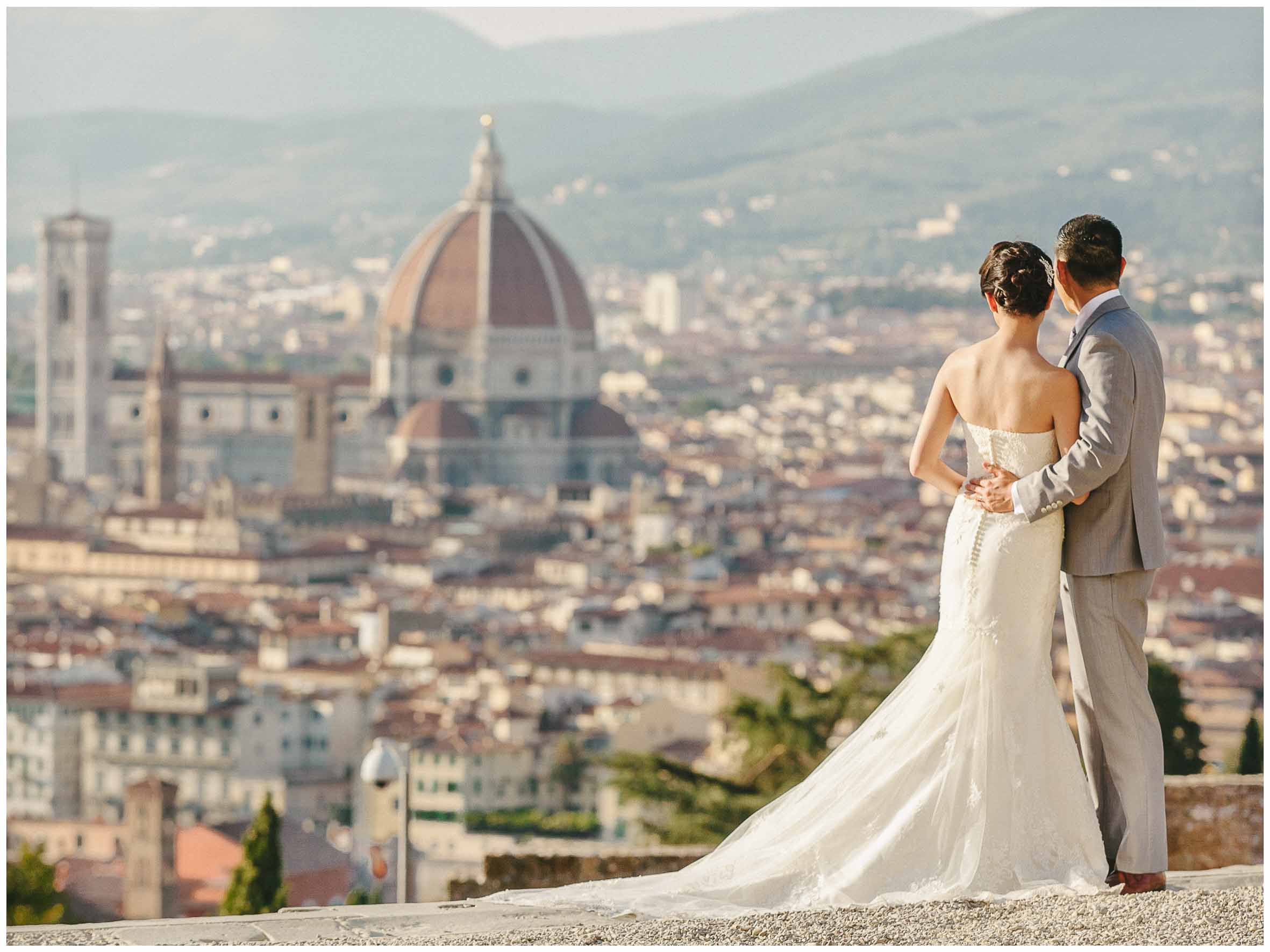 newlyweds hug each others with the dome of florence in the backgroud
