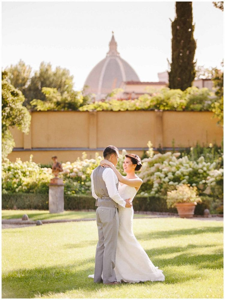 newlyweds posing the in the garden of the four seasons hotel in florence with the view of the dome