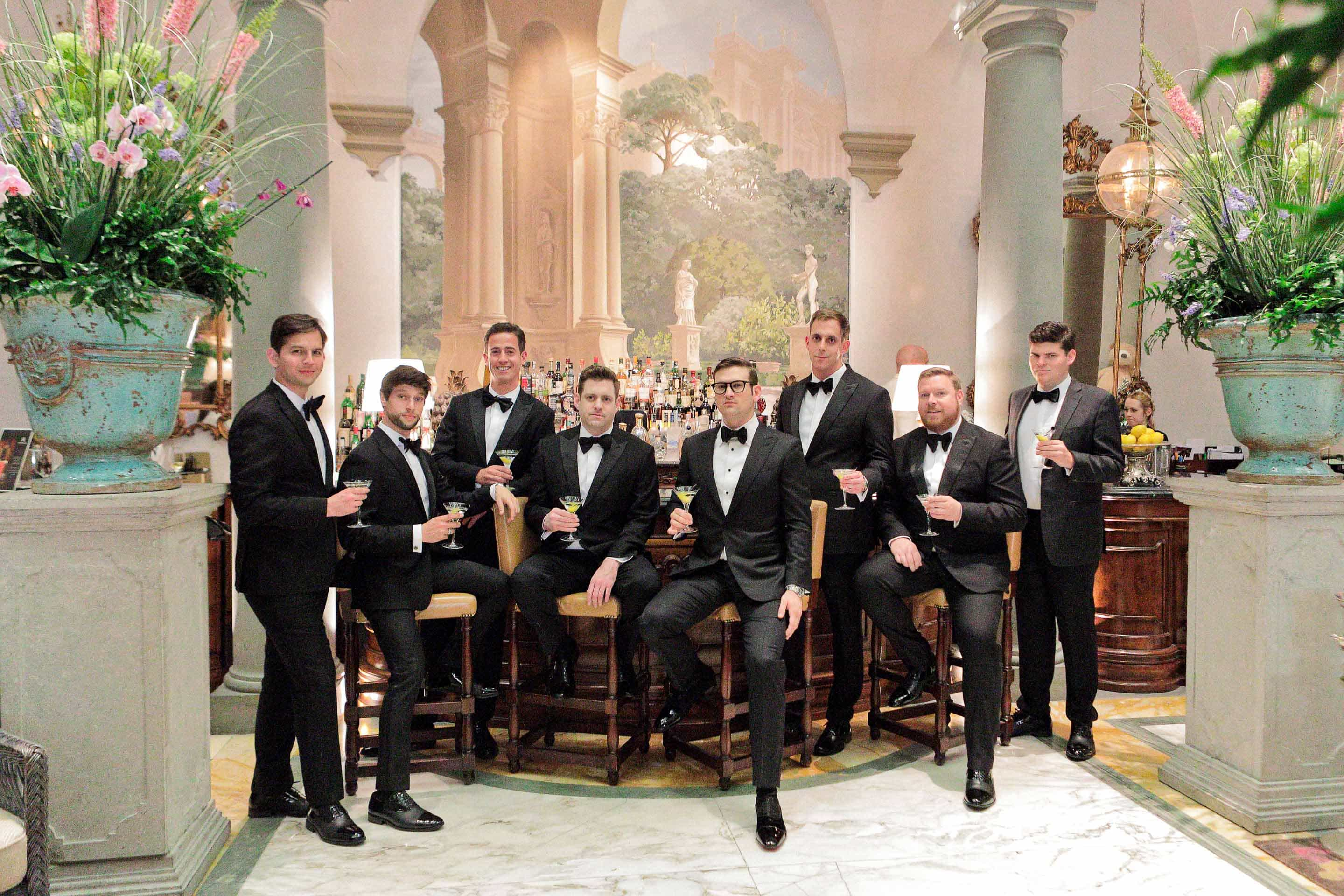groomsmen posing for the photographer in the hall of the st regis hotel of florence