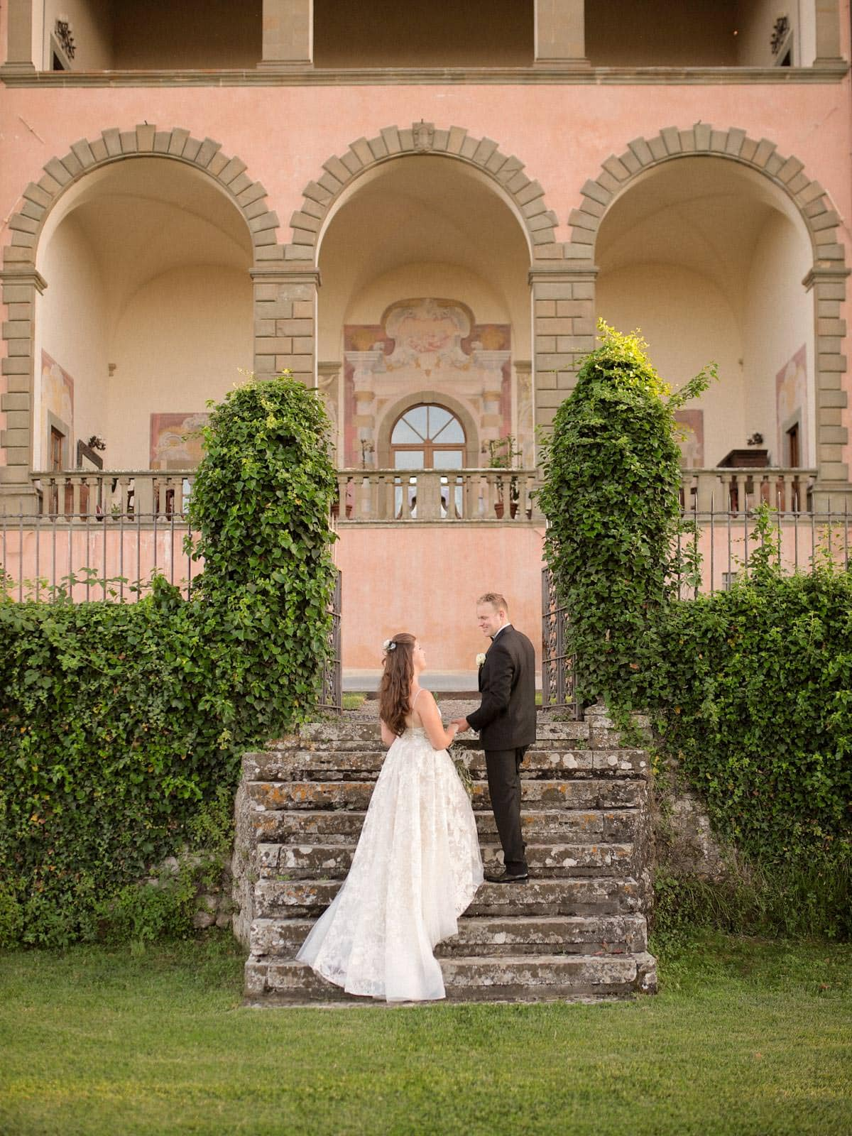 bride and groom walking up the steps with villa mangiacane in the background