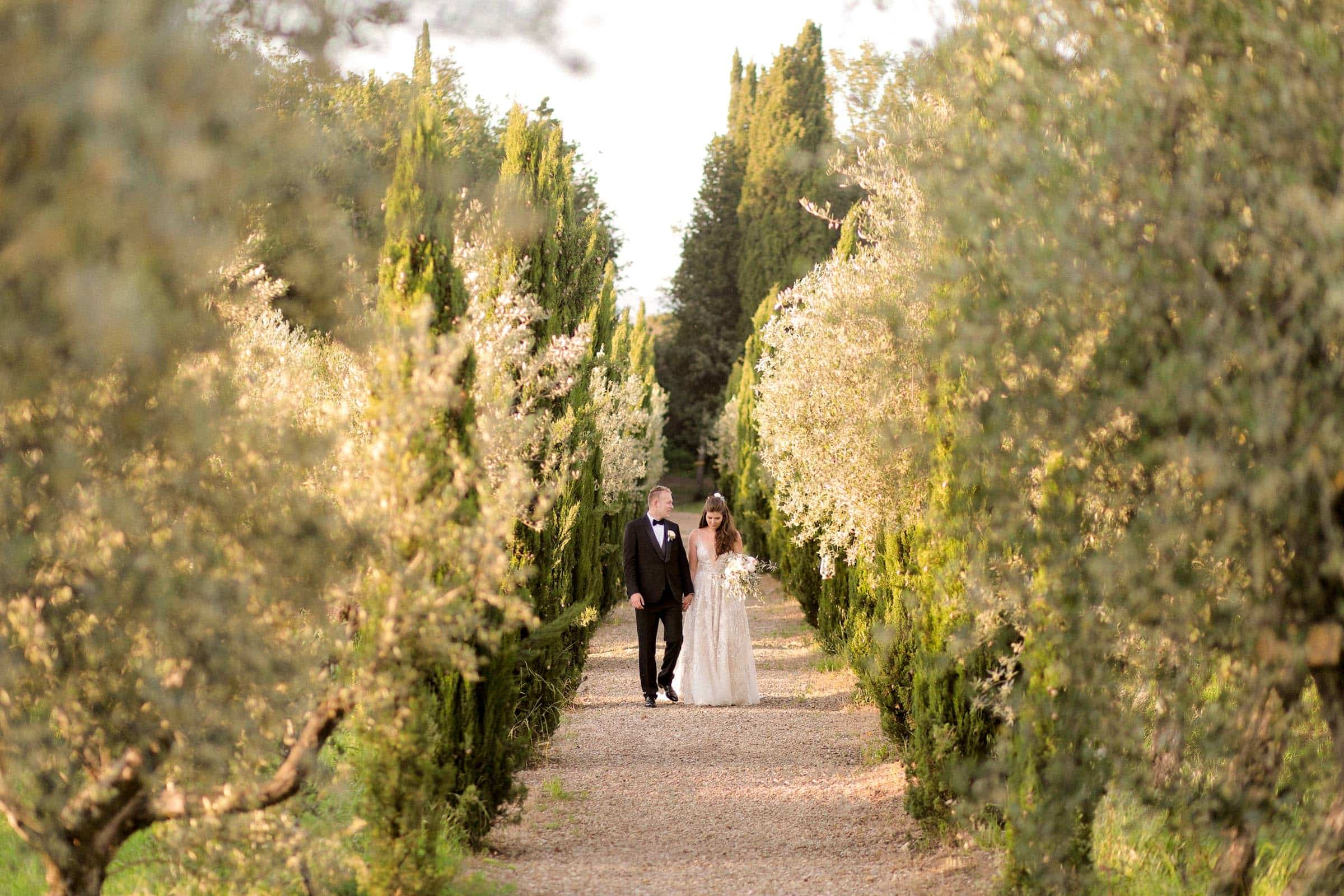 bride and groom walking up to the villa with cypress and olive trees all around