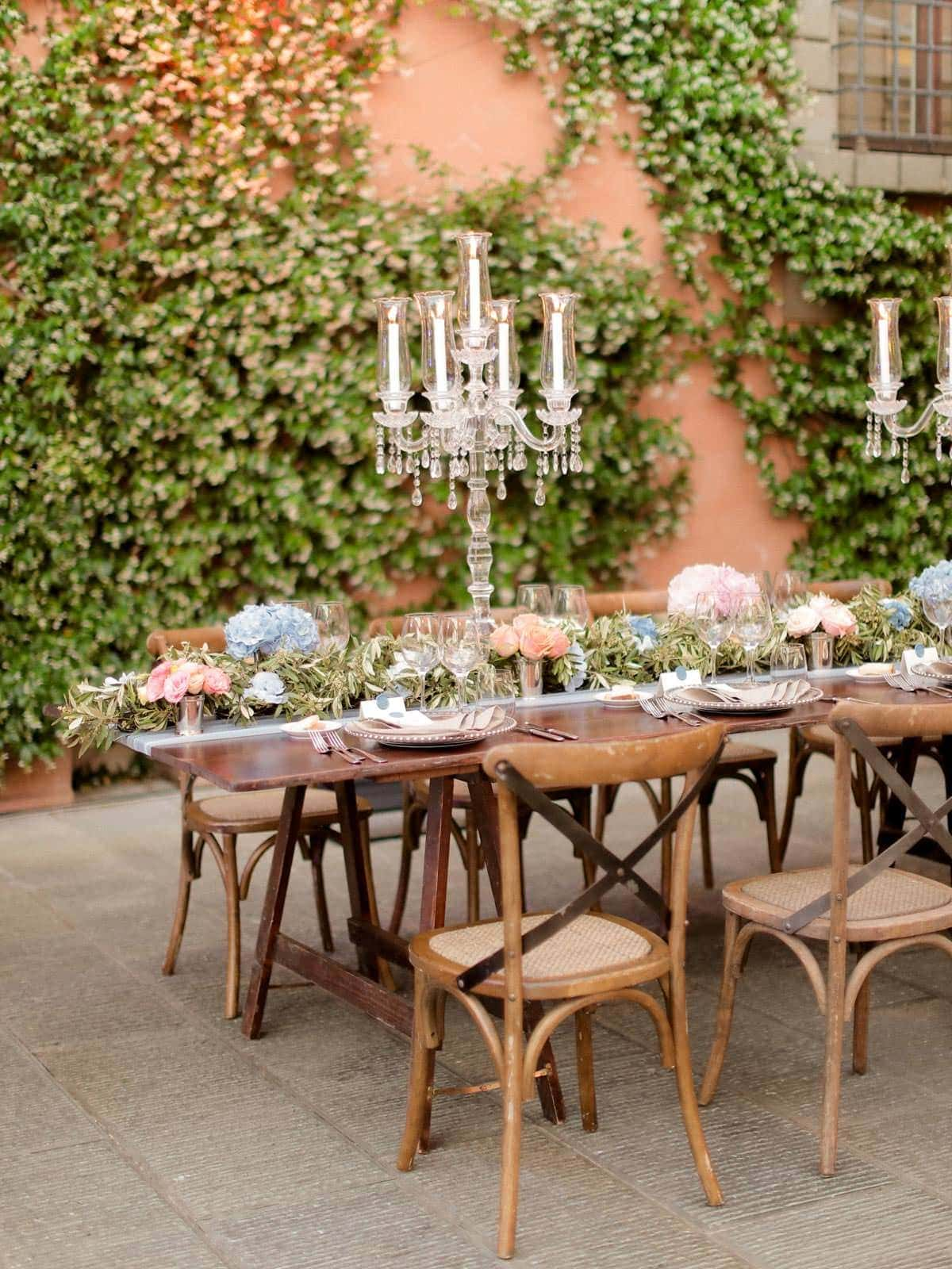 elegant table setting with long chandeliers and fresh pink flowers