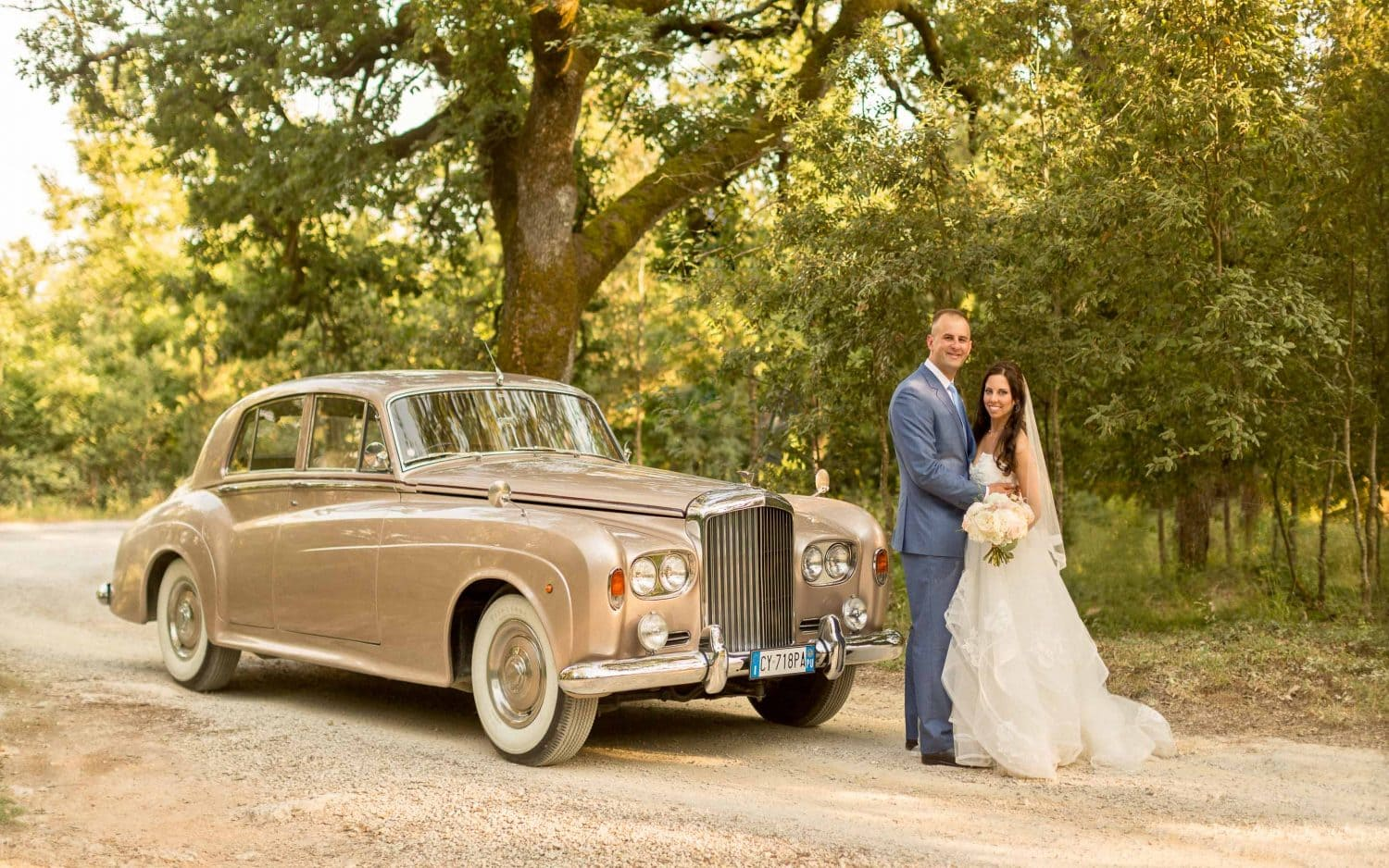 newlyweds with the bentley posing for the photographer